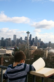 A young boy reads Braille with the Space needle in the background
