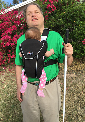 Darrell Shandrow poses with his child in a front carrier.