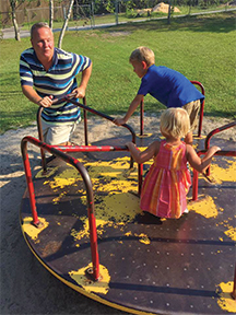 Dad spins his two children on the merry-go-round at the playground.
