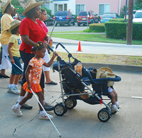 A group of people, several using canes, out for a stroll. A mother with a cane pushes a stroller while her blind child walks beside.