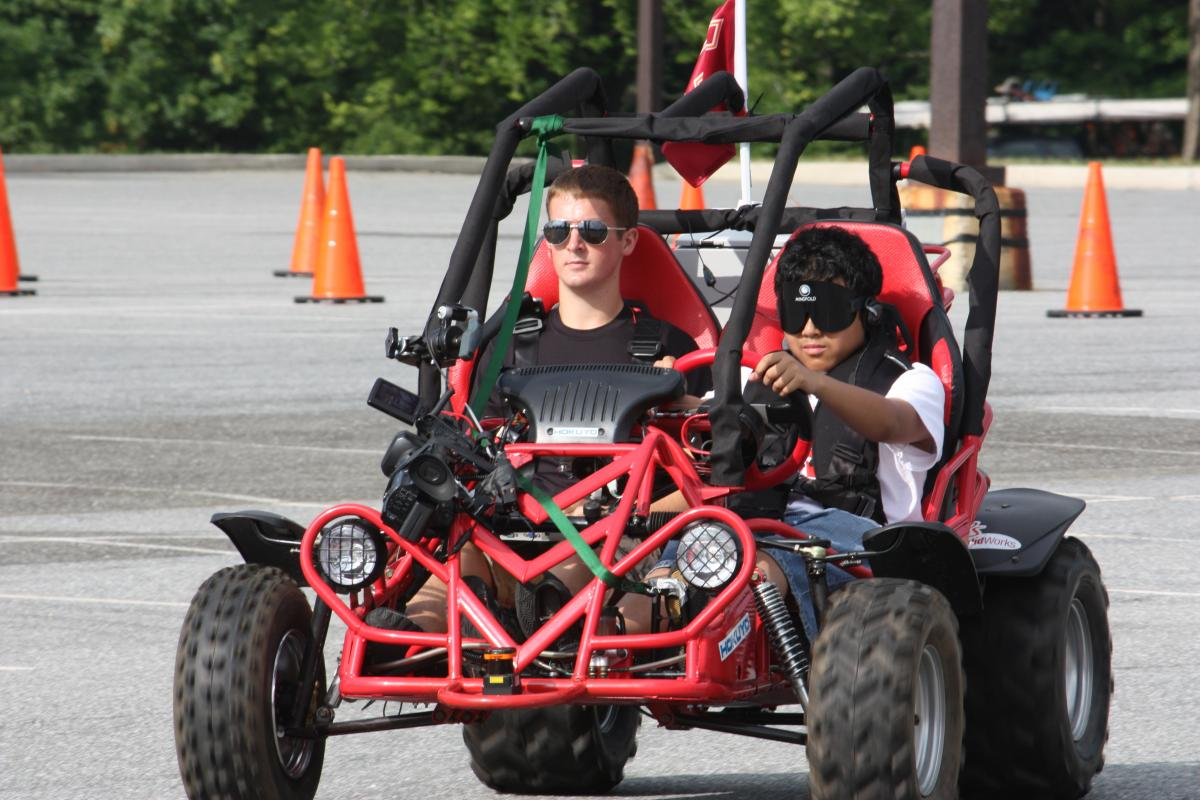 A student drives a dune buggy while under sleep shades at the NFB Youth Slam.