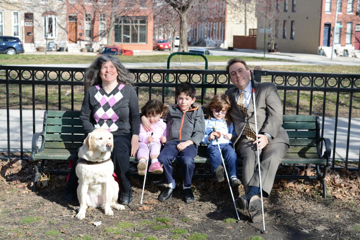 Melissa and Mark Riccobono sit smiling on a park bench with their children.