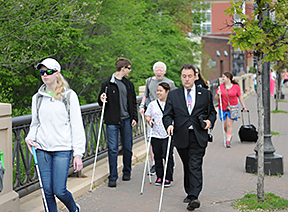 Blind youths and adults travel confidently with their long white canes.