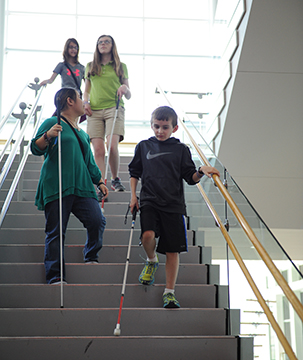 A group of blind youths walk confidently down the stairs with the help of their long white canes.