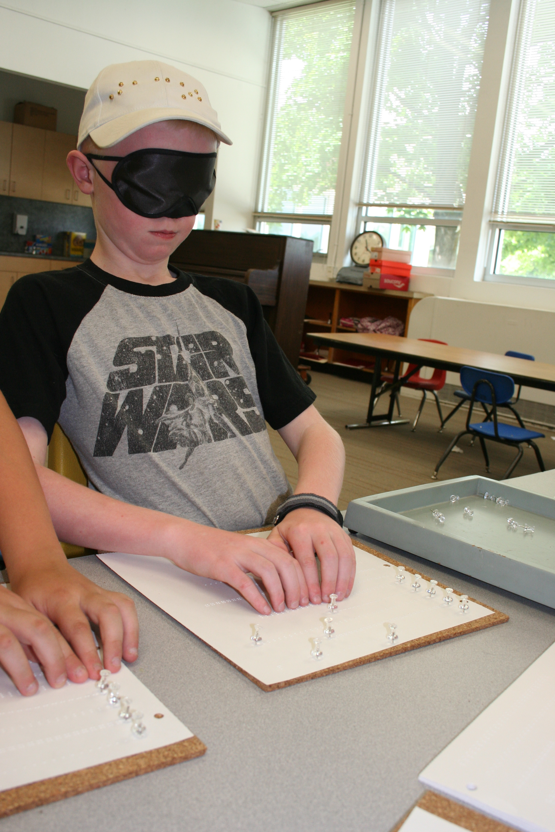 Jacob works on his Braille reading under sleep shades.