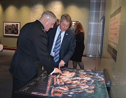 "Gen. Glenn Walters and John Paré examine the 3D rendition of ""The Tank."""
