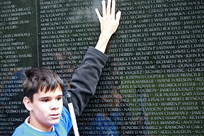 a teen boy holding a white cane strokes the surface of the Vietnam Veterans Memorial