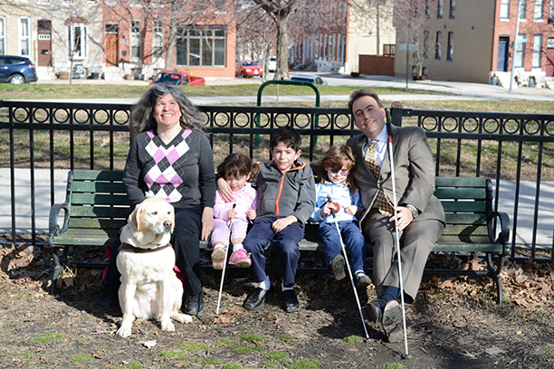 Melissa Riccobono and her family sit on a park bench.