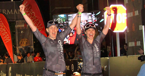 Randi and Caroline running through the finisher's shoot of Ironman Texas this year, holding hands with their arms raised in celebration.