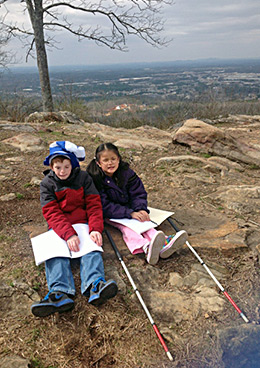 Two blind children reading atop Kennesaw Mountain in Georgia.
