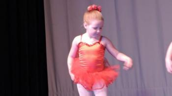 A girl on stage in a ballet costume.