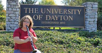 "A woman plays the clarinet while sitting in front of a sign that says ""The University of Dayton."""