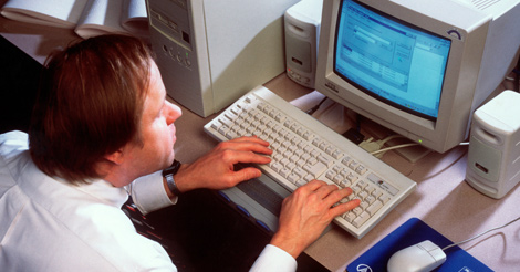 A professional man sits at a computer with his hands on the keyboard.