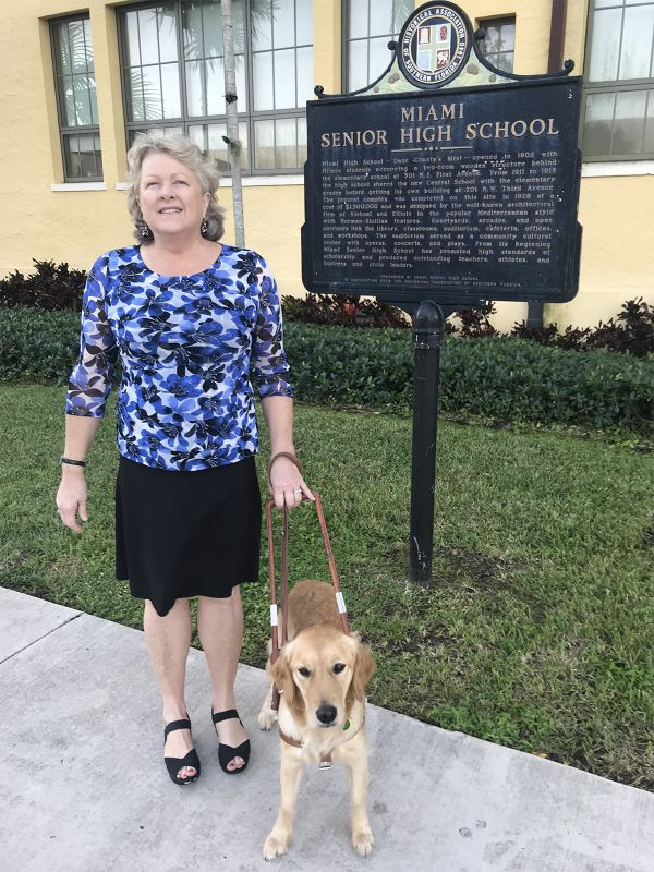 Dr. Janice Bartleson and her guide dog Dusty stand outside next to a Miami Senior High School sign.