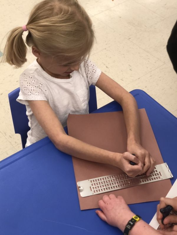 A young girls uses a slate and stylus.