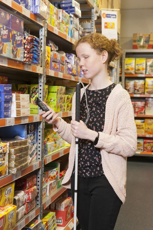 A girl stands in a grocery store cookie aisle holding a white cane in one hand and a smart phone in the other hand.