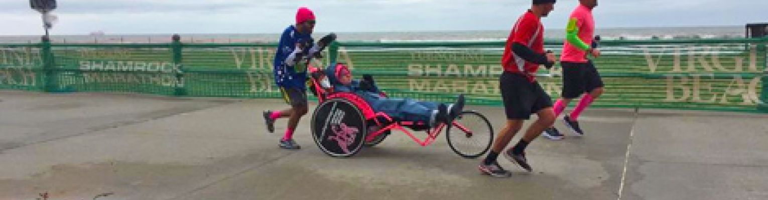 Michael pushes his friend Ashton in the Boston Marathon. Two other members of Team Hoyt run with them.