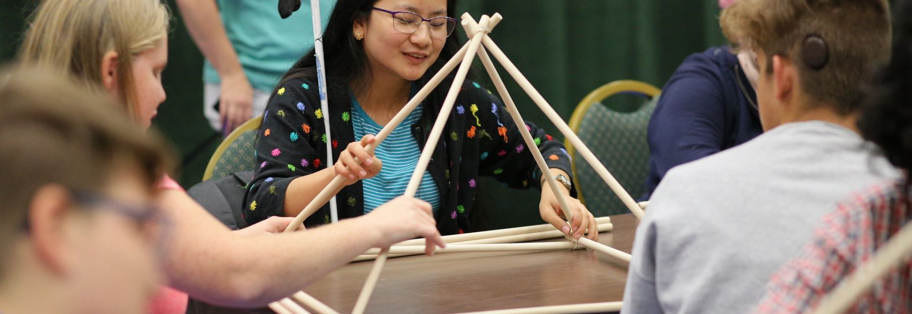 A girl builds a pyramid during an NFB STEM program for teens.