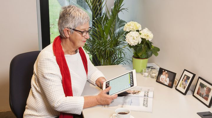 A woman holds a computer tablet over a magazine and smiles.