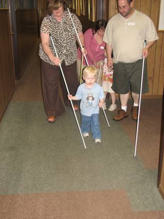 Amy Phelps teaching a young boy and his family how to use a white cane.