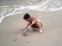 A blind boy plays on the beach with his cane.