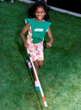 A young blind girl runs with her cane.