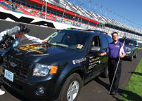 NFB Jernigan Institute executive director Mark Riccobono standing beside the BDC vehicle at Daytona International Speedway