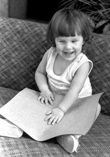 A young blind girl reading a Braille page.