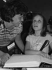 A child reading braille as her mother looks on