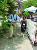 Two blind people taking a stroll using their long white canes.