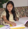 A blind girl reads a Braille book.