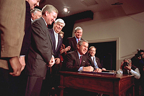 President George Bush surrounded by staff, signing the Help America Vote Act on October 29, 2002.
