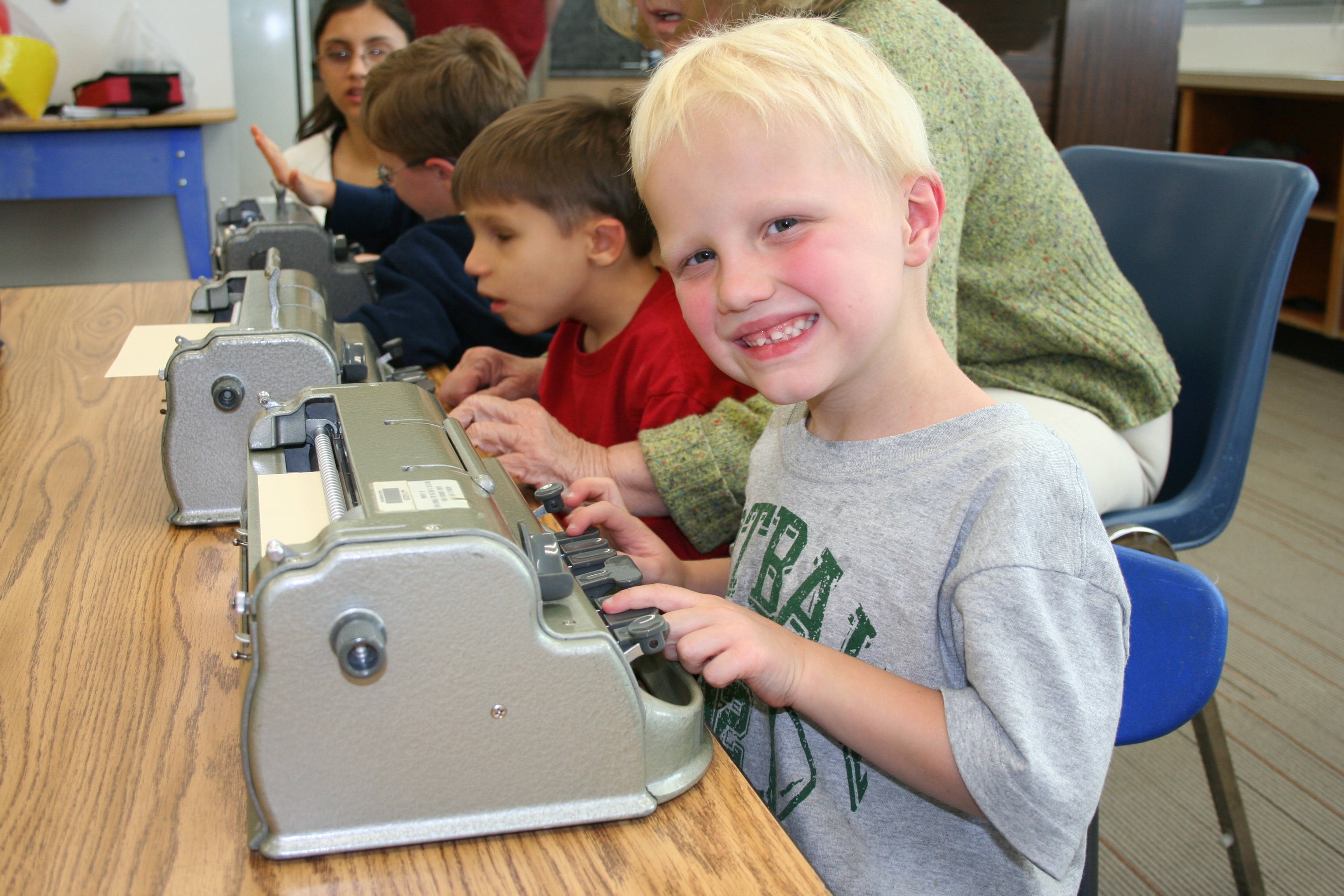 Riley Phelps of the Utah BELL session smiles next to his Braillewriter.