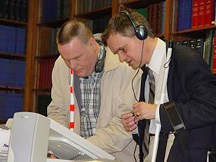 Steve Booth, one of NFB's access technology specialists, helps a blind voter use an accessible voting machine.