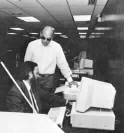 Mr. Chong at a computer discussing technology with visitors