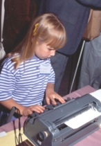 Young girl uses a Braillewriter.
