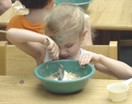 A little girl, Jodi Jones, stirs ingredients in a bowl.
