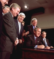 President George Bush, surrounded by staff, signs the Help America Vote Act on October 29, 2002.