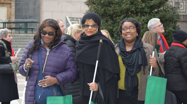 Three black, blind women smile while waiting outside of representative building during previous Washington Seminar
