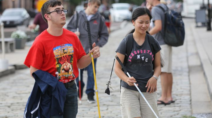 Two blind people walk on a sidewalk using white canes.