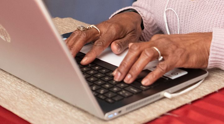 Black person typing on computer