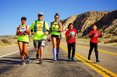 Terri Rupp runs alongside her guides and her two children.