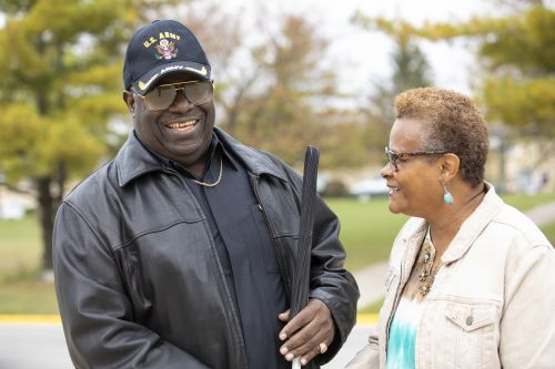 A man wearing a U.S. Army hat smiles as he holds a long white cane outside; a woman stands next to him also smiling.