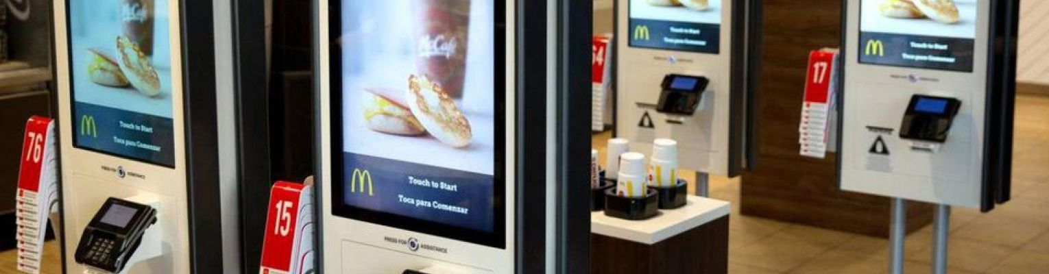 "Four touch screen devices with McDonald's logo that say, ""Order Here"""